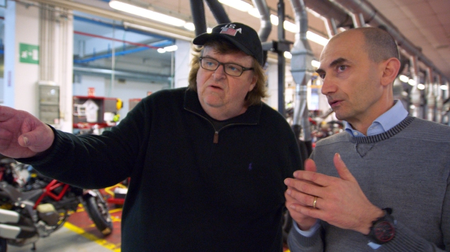 """This image provided by Dog Eat Dog Films shows director Michael Moore, left,  and Claudio Domenicali, CEO of Ducati, in a scene from his documentary, """"Where to Invade Next."""" The movie opens in U.S. theaters on Feb. 12, 2016. (Dog Eat Dog Films via AP)"""