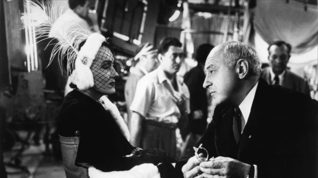 Cecil B. DeMille (playing himself) reunites with his former silent-era starlet