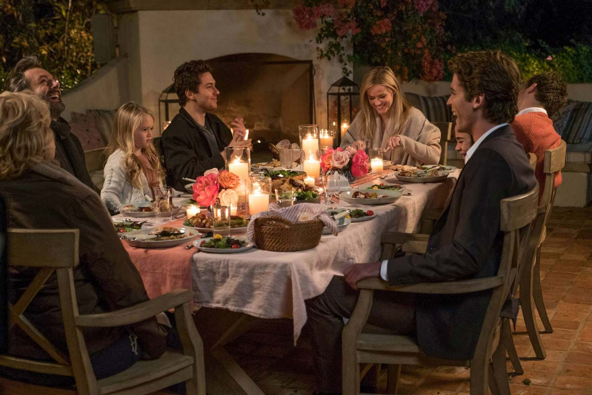 The cast of HOME AGAIN (2017) in an outdoor dinner scene