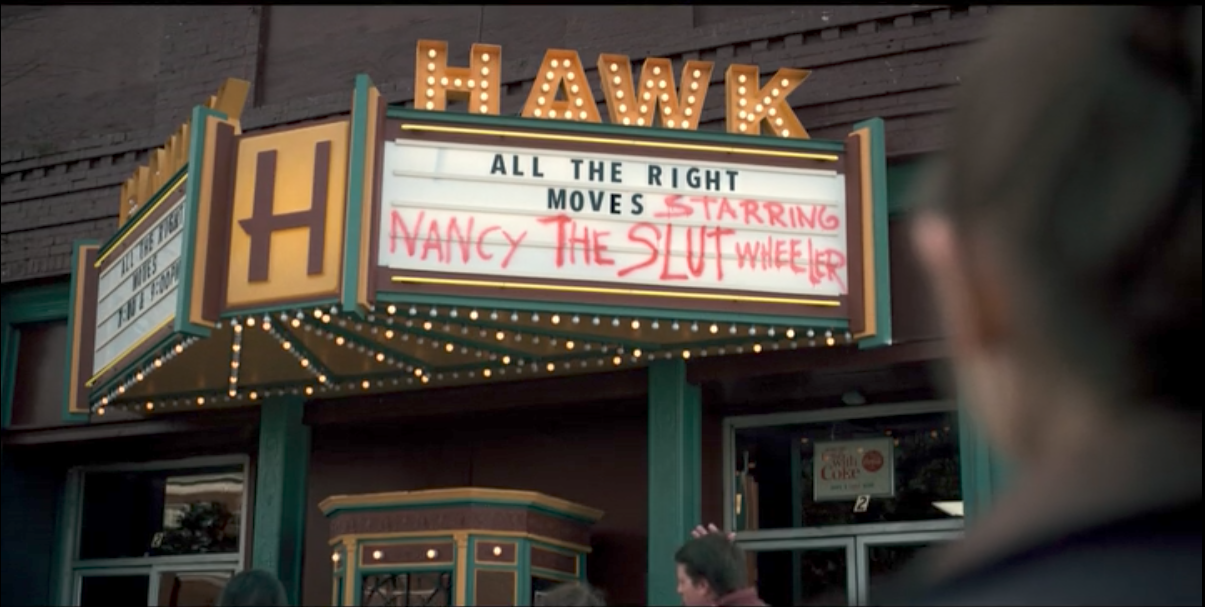 """The movie marquee in Hawkins in STRANGER THINGS (2016). The official movie showing is ALL THE RIGHT MOVES, with """"Starring Nancy The Slut Wheeler"""" scrawled in spray paint next to the title"""